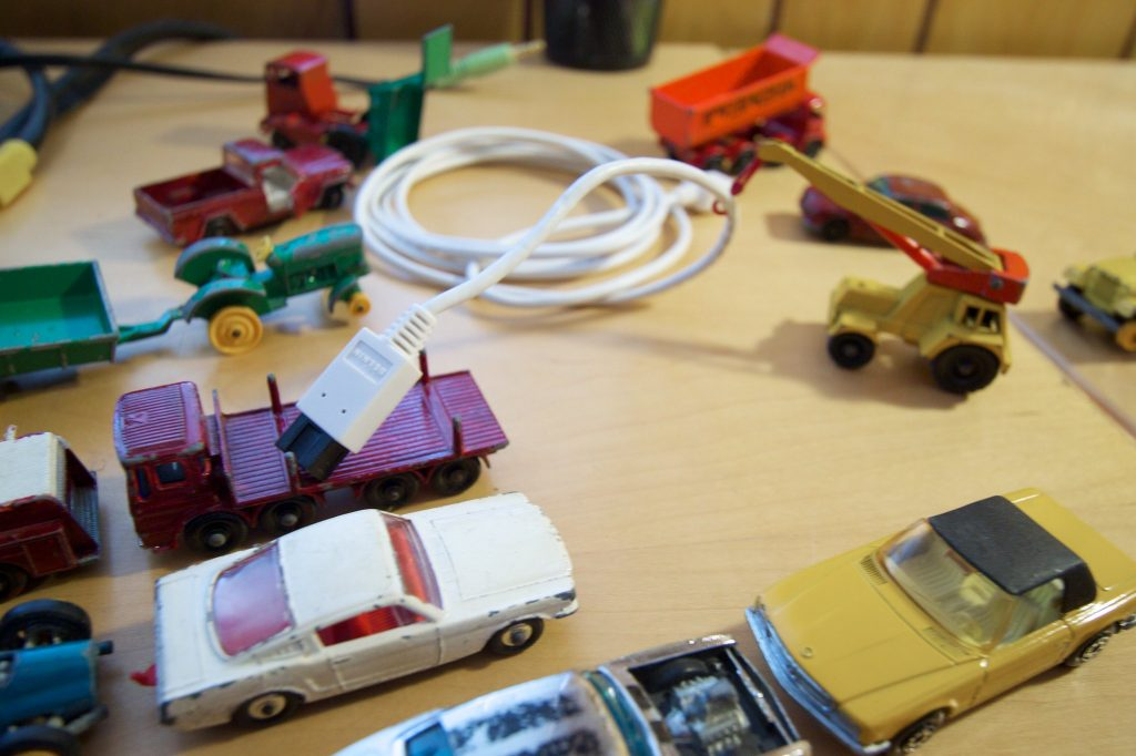 Toy cars on a table top, a crane is lifting a USB cable into the back of another truck